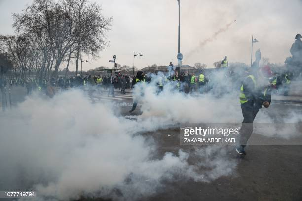 TOPSHOT Yellow vest Gilets Jaunes antigovernment protestors dodge clouds of teargas during clashes with security personnel at a rally in Paris on...