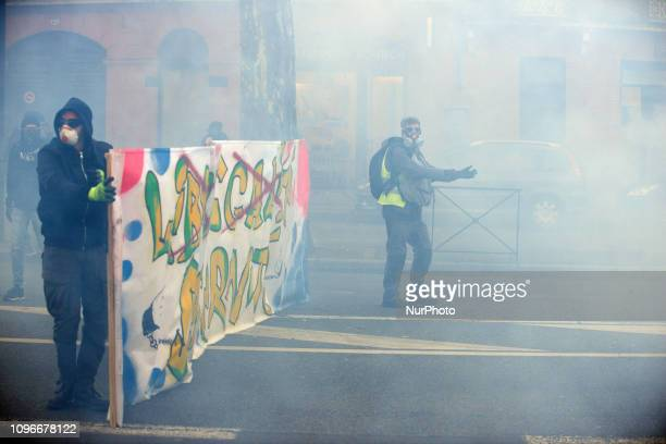 A Yellow Vest man and protesters hold a banner amid clouds of tear gas Act XIII dubbed 'Civil disobediencequot' of the Yellow Vest movement begun...