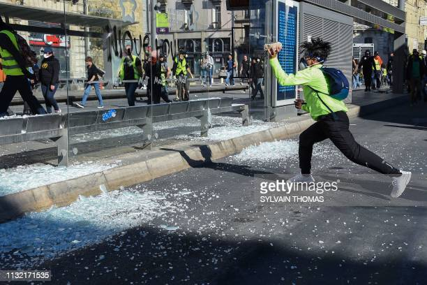 TOPSHOT A yellow Vest protester breaks the glass window of a tram stop with a stone as he takes part in an antigovernment demonstration in...