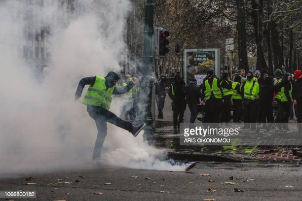 A Yellow vest protester kicks back a tear gas canister during clashes as part of a demonstration on November 30 near major EU buildings in Brussels...