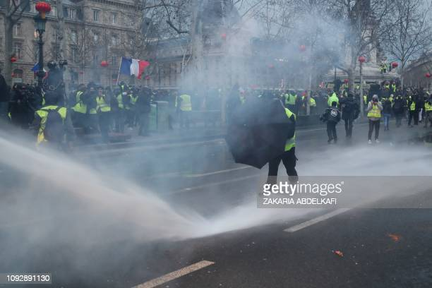 Yellow vest protester shields himself behind an umbrella as he stands in front of a water cannon during clashes with police forces on the Place de la...