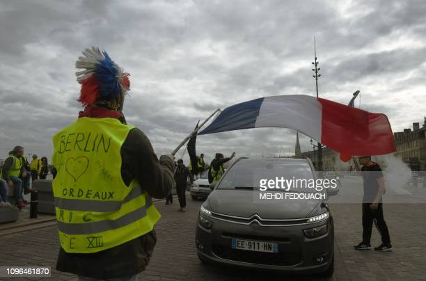 Yellow Vest protester waves a French national flag as they partially block a road in Bordeaux, southwestern France, on February 9 as they take to the...