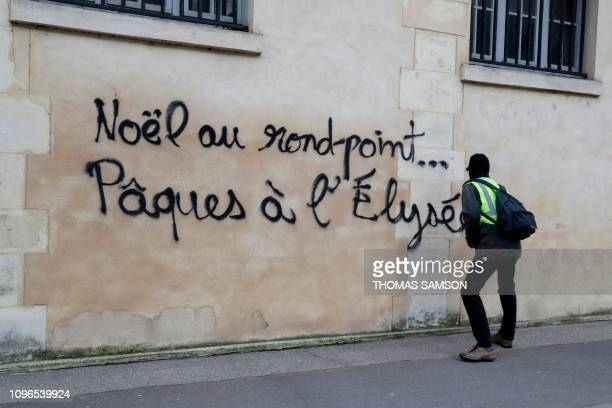 A yellow vest protester writes on a wall Christmas on a roundabout Easter at the Elysee palace as he takes part in the 13th consecutive Saturday of...