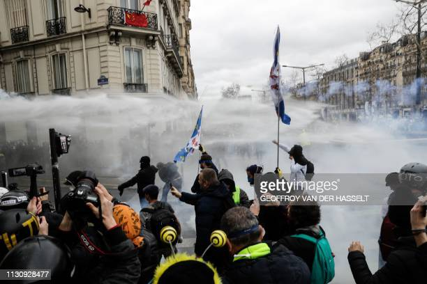 Yellow Vest protesters receive water from a water cannon during clashes with riot police forces in Paris on March 16 during the 18th consecutive...