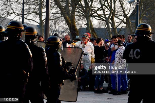 Yellow Vest protesters stand before riot policemen during an antigovernment demonstration called by the 'Yellow Vest' movement in Metz on March 23...