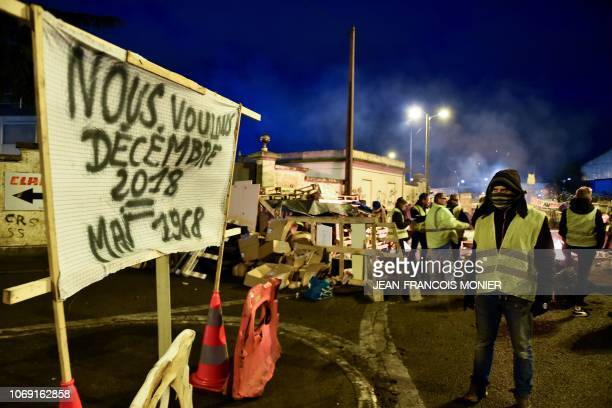 TOPSHOT A yellow vest protestor looks at a banner reading We want December 2018 = May 1968 on a baricade blocking the access to the oil depot on...