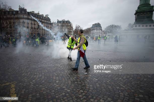 A yellow vest protestor throws back the tear gas cannister to the police during a demonstration against macron policies Yellow vest protestors...