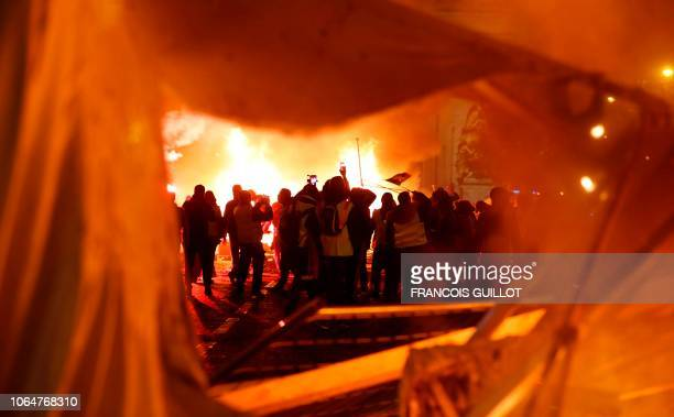 Yellow vest protestors are seen through a damaged hoarding as they throw material onto a fire on the ChampsElysees in Paris on November 24 during a...