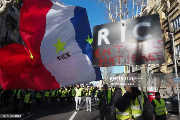 TOPSHOT Yellow vest protestors demonstrate with placards reading 'RIC' for Citizens' Initiative Referendum in Perpignan southern France on January 5...