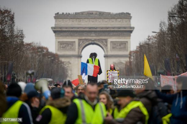 TOPSHOT Yellow vest protestors hoist an effigy with a French national flag in front of The Arc de Triomphe on The ChampsElysees in Paris on January 5...