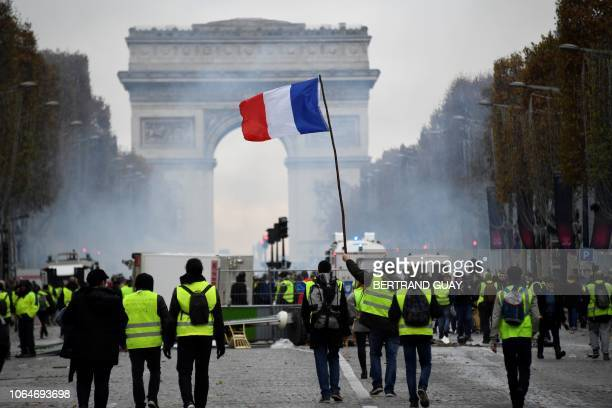 TOPSHOT Yellow vest protestors hold a French flag on the Champs Elysees in Paris on November 24 2018 during a protest against rising oil prices and...