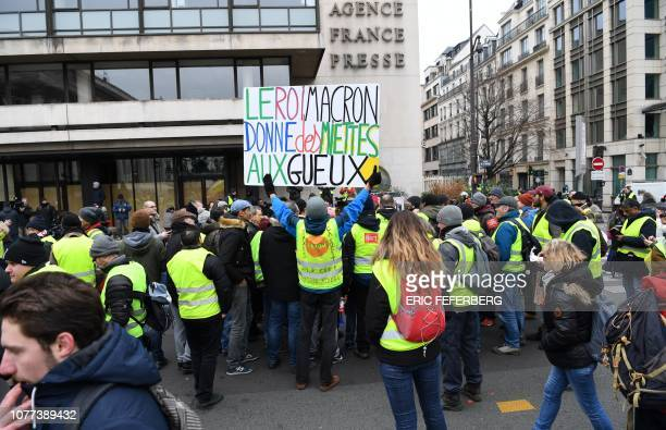 Yellow vest protestors stand with a sign which translates as ' King Macron give crumbs to the beggars' as they gather outside Agence FrancePresse...