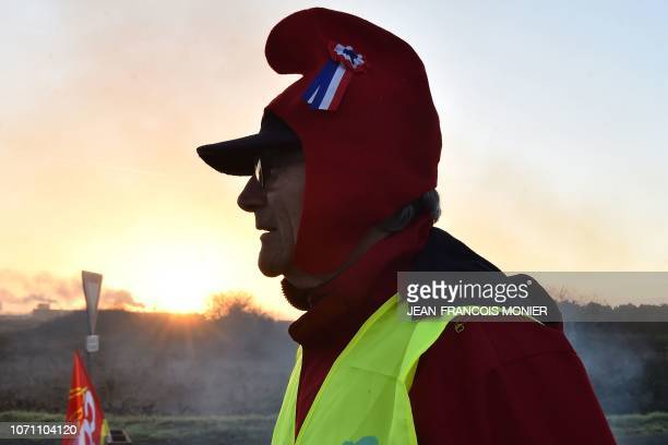 TOPSHOT A 'Yellow vests' protester wears a Phrygian cap during a rally to block the access to the 'Carrefour Supply Chain' the regional logistics...