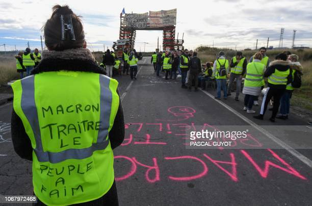 A Yellow vests protester with the words written of the back of her vest that read ' Macron traitor the people are hungry' blocks the road leading to...