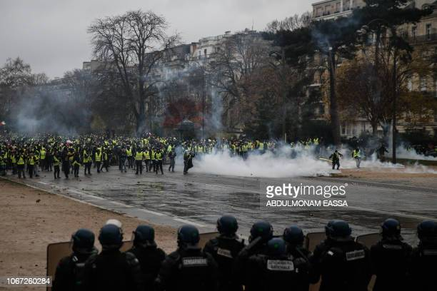 TOPSHOT Yellow vests protesters face riot police as they demonstrate against rising oil prices and living costs on December 1 2018 in Paris