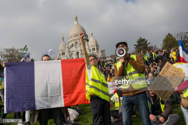 Yellow vests protesters march in front of the SacreCoeur Basilica of Montmartre during the Act 19 protest called for by the Gilets Jaunes on March 23...