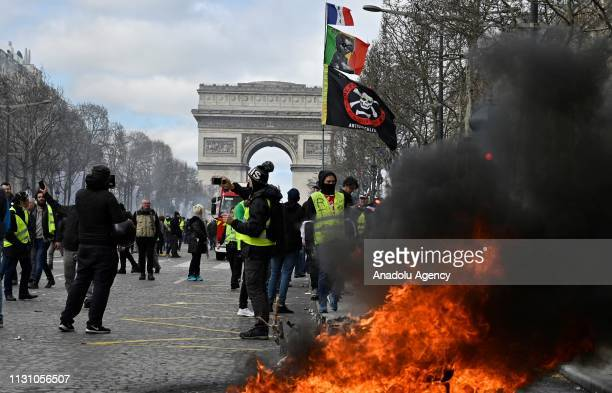 Yellow vests protesters setup a barricade with fire on the ChampsElysees during the 18th consecutive Saturday national protest in Paris France on...