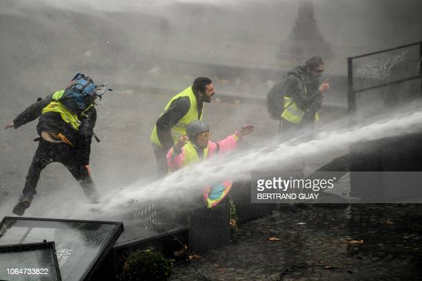 TOPSHOT Yellow vests protestors are showered by a water cannon near the Place de la Concorde in Paris on November 24 during a protest against rising...