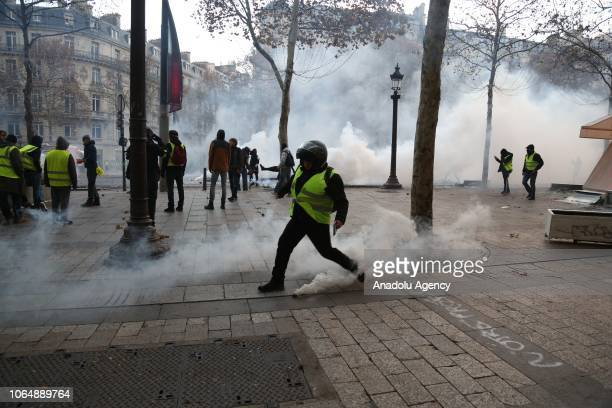 Yellow vests protestors clash with riot police during a protest against rising oil prices on the Champs Elysees in Paris France on November 24 2018...