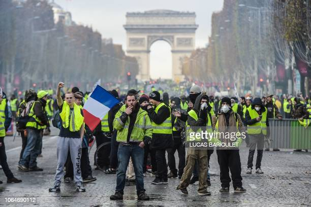 Yellow vests protestors demonstrate near the Arc de Triomphe on the Champs Elysees in Paris, on November 24, 2018 during a protest against rising oil...
