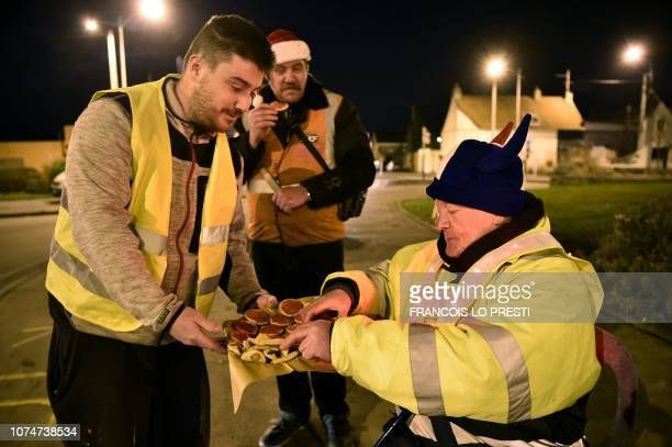 Yellow vests protestors eat as they spend Christmas eve on a roundabout in Somain northern France on December 24 2018 French President called for...