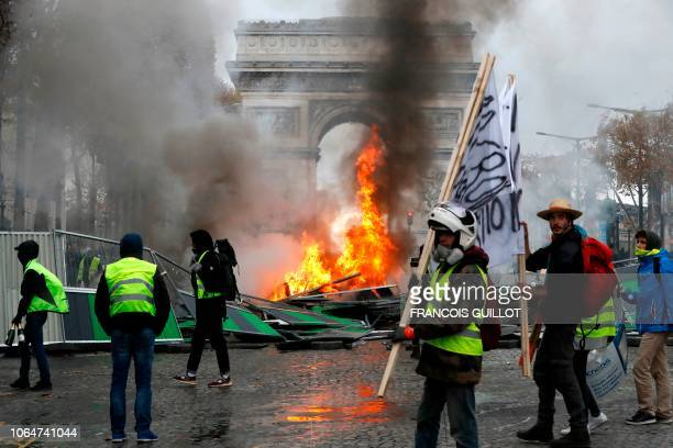 Yellow vests protestors gather as material burns during a protest against rising oil prices and living costs near the Arc of Triomphe on the Champs...