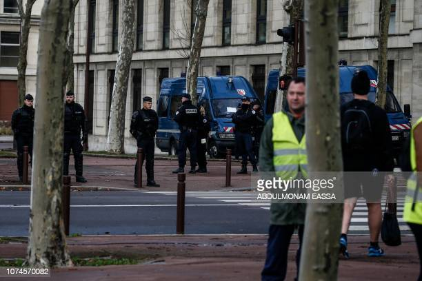 'Yellow Vests' protestors gather next to police officers ahead of a demonstration in front of the Chateau de Versailles in Versailles outside Paris...