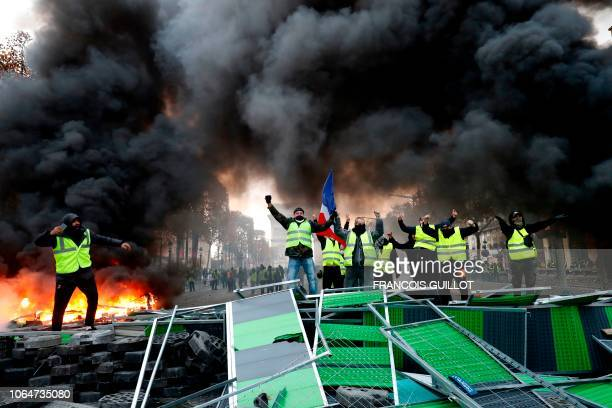 TOPSHOT Yellow vests protestors shout slogans as material burns during a protest against rising oil prices and living costs near the Arc of Triomphe...