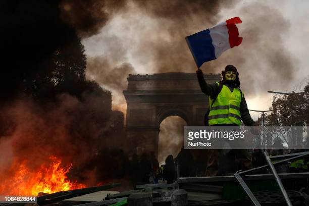 Yellow vests protestors shout slogans as material burns during a protest against rising oil prices and living costs near the Arc of Triomphe on the...