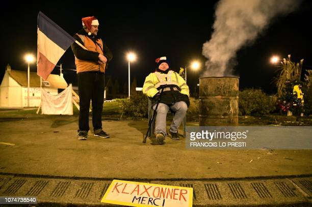 TOPSHOT Yellow vests protestors stand near a sign reading 'Thank you for honking' as they spend Christmas eve on a roundabout in Somain northern...