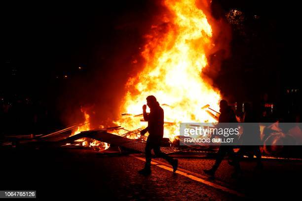 Yellow vests protestors walk past burning material on the ChampsElysees in Paris on November 24 during a protest against rising oil prices and living...
