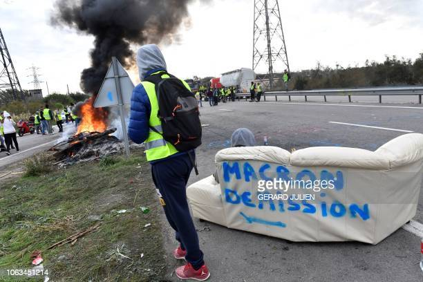 Yellow Vests stand near a fire and a couch bearing Macron resign as they block a road during a demonstration against the rising of the fuel and oil...