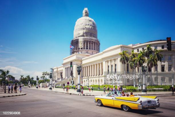 yellow vintage car in front of capitolio in havana. cuba - havana stock pictures, royalty-free photos & images