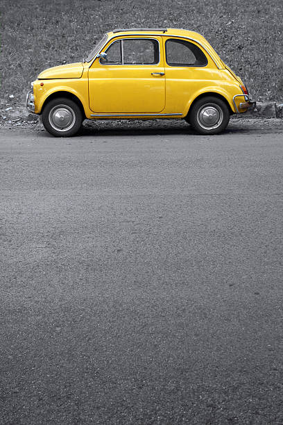 Yellow vintage car on grey, Rome Italy