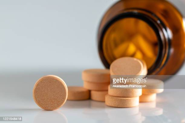 yellow vitamin pills isolated on a white background - vitamin c stock pictures, royalty-free photos & images