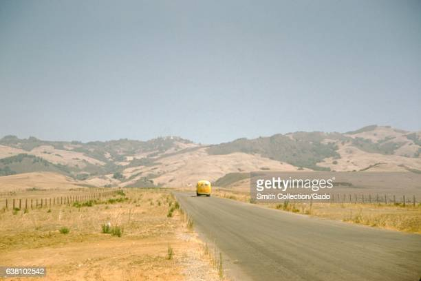 A yellow Volkswagen bus travels along a country road that cuts through a prairie covered in dry grass low rolling hills can be seen in the background...
