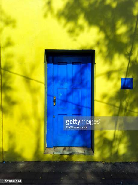 yellow wall and the blue door. - crmacedonio bildbanksfoton och bilder