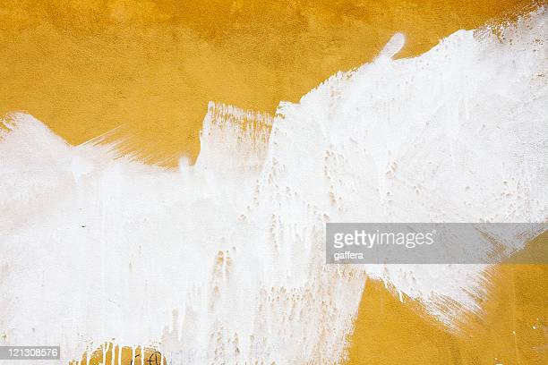 a yellow wall splashed with white paint - paint stock pictures, royalty-free photos & images