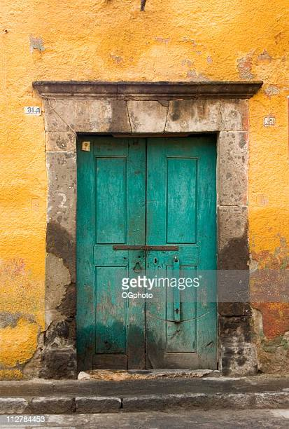 yellow wall with green door. - ogphoto stock pictures, royalty-free photos & images