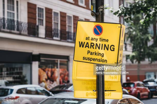 yellow warning parking suspension sign on a residential street in london, uk. - parking stock pictures, royalty-free photos & images