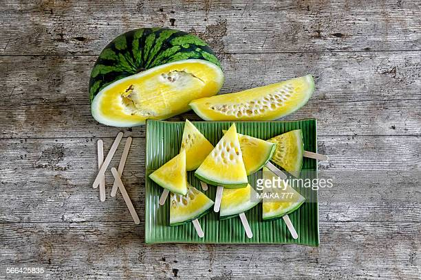 Yellow watermelon slices on a popsicle stick