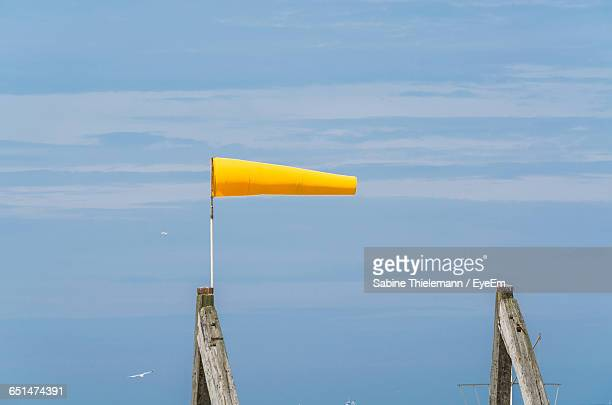 Yellow Windsock On Wood Against Sky