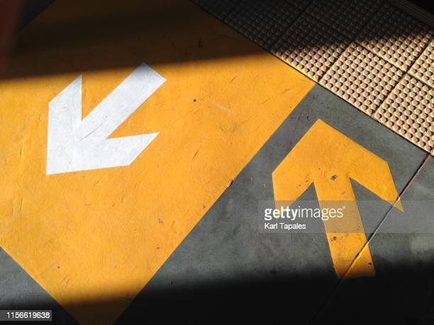 yellow-colored arrows symbol - richtung stock-fotos und bilder