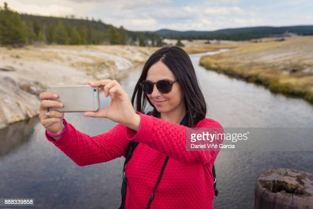 Yellowstone national park, young woman taking a selfie with her smartphone