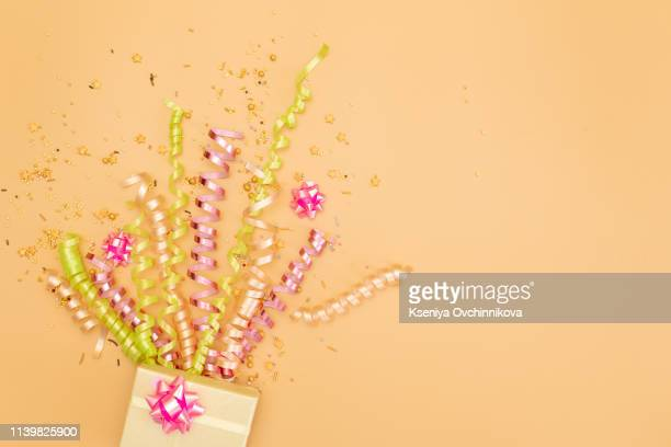 yelow gift box with various party confetti, streamers, noisemakers and decoration on a orange background. colorful celebration background. - streamer stock pictures, royalty-free photos & images