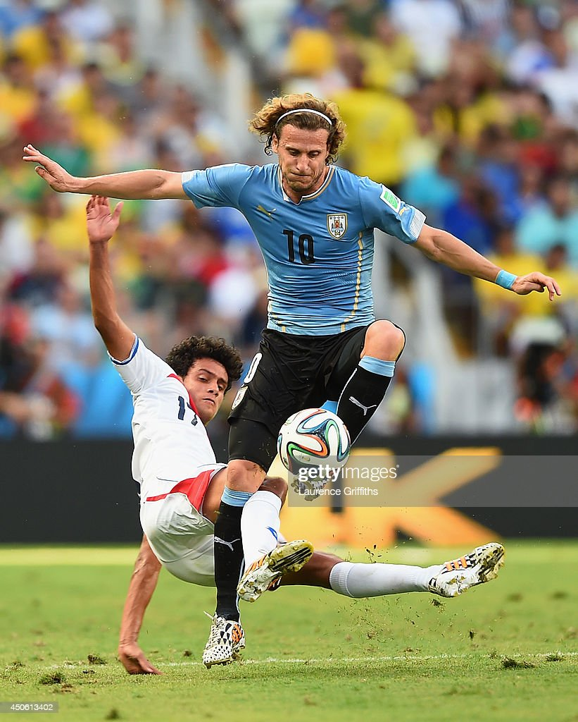 Yeltsin Tejeda of Costa Rica tackles Diego Forlan of Uruguay during the 2014 FIFA World Cup Brazil Group D match between Uruguay and Costa Rica at Castelao on June 14, 2014 in Fortaleza, Brazil.