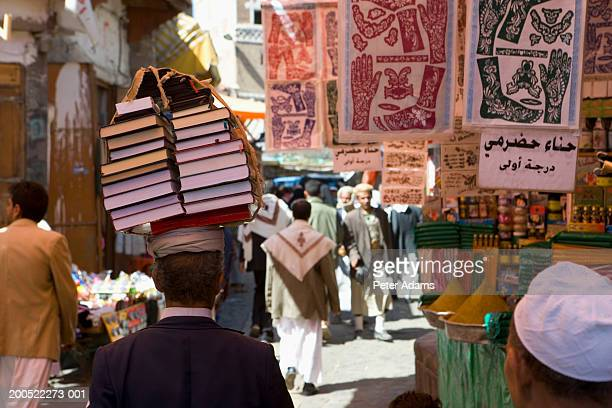 yemen, bookseller walking with books balanced on head in market - yemen stock pictures, royalty-free photos & images