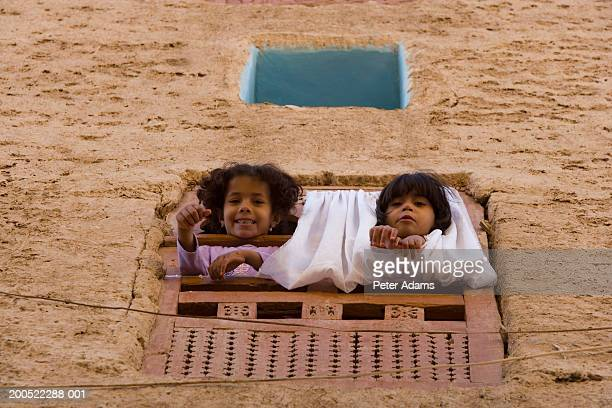 yemen, boy and girl (6-8) leaning out of window, smiling, portrait - yemen stock pictures, royalty-free photos & images
