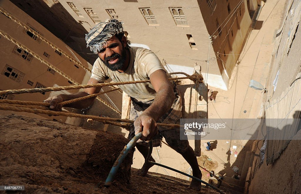 Yemen Hadhramaut Shibam - reconstruction of the old town with ancient mudbrick buildings, worker is preparing mudbrick : News Photo