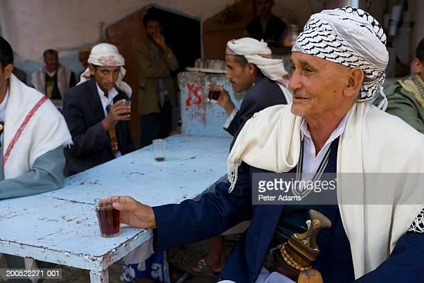 Yemen, San'a Province, senior man drinking tea, smiling